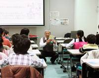 A yen for knowledge: Masayuki Osaki, a former Tokyo Stock Exchange employee, teaches economic and financial matters to children at the TSE on April 2. | KYODO PHOTO