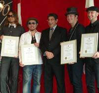 Top billing: Members of Canadian-Japanese pop-rock band Monkey Majik pose with Canadian Ambassador to Japan Jonathan Fried (center) at a ceremony Wednesday at the Canadian Embassy in Tokyo.   KYODO PHOTO