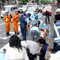 First responders: Rescue workers treat people hit by a car while walking on a sidewalk Sunday in Shimogyo Ward, Kyoto.   KYODO PHOTO