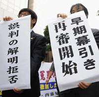 Warning signs: Toshikazu Sugaya, freed earlier this month after spending 17 years in prison for an apparently wrongful conviction, holds a news conference Tuesday in Tokyo. Above: Sugaya's lawyers hold up banners at the Tokyo High Court saying his retrial will not review why he was wrongfully convicted. | KYODO PHOTO
