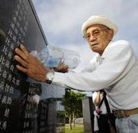 Remembering: A relative of a victim of the Battle of Okinawa pours water Tuesday on a cenotaph engraved with names of the dead at Peace Memorial Park in Itoman, Okinawa Prefecture. | KYODO PHOTO