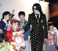 Better times: Michael Jackson smiles while posing for a photo with children from a Tokyo orphanage who were invited to an exculsive fan event in Tokyo on March 8, 2007.   AP PHOTO