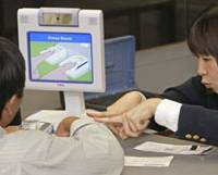 Hard to fool: Immigration officers at Narita International Airport demonstrate the biometric identification system to the media in November 2007. | KYODO PHOTO
