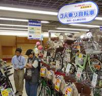 Bicycle built for three: A shopper examines bicycles designed to carry one adult and two children at a store in Shinjuku Ward, Tokyo, on Wednesday. | KYODO PHOTO