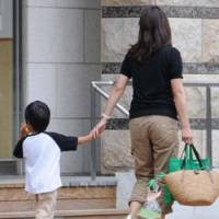 Time for a stroll: A mother and child take a walk in a park in Minato Ward, Tokyo, on Tuesday. | SATOKO KAWSAKI PHOTO