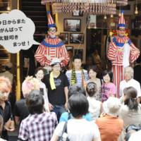 Back beat: Visitors have their picture taken in front of the mechanical drummer man Kuidaore Taro (left), which returned to Osaka's Dotonbori area Sunday, and his 'younger brother' Kuidaore Jiro. | KYODO PHOTO