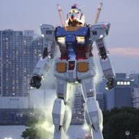 Bow down: An 18-meter tall Gundam statue towers over admirers at a Tokyo park on July 11. The full-size model of Japan's popular animated robot character was erected to mark the 30th anniversary of the start of the TV series 'Mobile Suit Gundam.' | AP PHOTO
