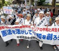 Give peace a chance: Relatives of the war dead who oppose politicians' visits to Yasukuni Shrine march near the controversial site in Chiyoda Ward, Tokyo, on Saturday with a banner calling for peace based on the Constitution.   YOSHIAKI MIURA PHOTO