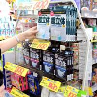 Preventive step: A drugstore in Minato Ward, Tokyo, displays face masks Thursday. Customers are stocking up as the new H1N1 virus claims its first domestic fatalities. | SATOKO KAWASAKI PHOTO