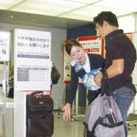 Travel light: A flight attendant shows a passenger Wednesday what the new size and weight limits for a carry-on bag will be when new baggage rules take effect at Haneda airport in Tokyo in December. | KYODO PHOTO