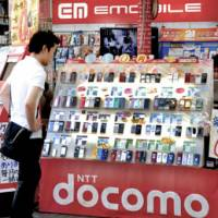 All the bells and ring tones: A man takes a look at the latest cell phone models at a store in the Akihabara district of Chiyoda Ward, Tokyo. | YOSHIAKI MIURA PHOTO