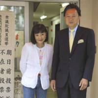 Unorthodox: Democratic Party of Japan leader Yukio Hatoyama and his wife, Miyuki, pose for the media after casting their absentee votes for last Sunday's general election at a polling station in Tokyo on Aug. 26. | AP PHOTO