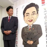Yukio Hatoyama stands next to a poster featuring 'Yukio-chan,' an illustrated likeness of him drawn up to represent the Democratic Party of Japan, at DPJ headquarters in July 2001 when he was party president. | KYODO PHOTO