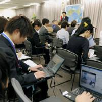 Broader access: Employees of Internet media sites broadcast a news conference live by Foreign Minister Katsuya Okada on Sept. 29. In the past, only press club members were allowed to attend briefings at the ministry.   KYODO PHOTO