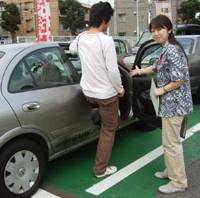 Signal your intent: An instructor escorts her student to a vehicle at the Musashi-Sakai Driving School in Musashino, western Tokyo, in August.   KYODO PHOTO