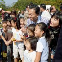 Mixing: Prime Minister Yukio Hatoyama and his wife, Miyuki, take part in a community event Sunday in Ota Ward, Tokyo, aimed at preserving nature in urban neighborhoods. | KYODO PHOTO
