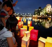 Cause for hope: Paper lanterns are released on the Motoyasu River against the backdrop of the Atomic Bomb Dome in Hiroshima on Aug. 6 as the city marked the 64th anniversary of the world's first atomic bomb attack. | AP PHOTO