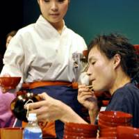 Noodle queen: Hatsuyo 'the Witch' Sugawara wolfs down bowls of 'soba' noodles Sunday during an eating competition in Morioka, Iwate Prefecture.   KYODO PHOTO