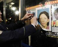 Out of circulation: A police officer peels off a wanted poster of Tatsuya Ichihashi after he was arrested Tuesday. | KYODO PHOTO
