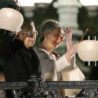 Aglow: Emperor Akihito and Empress Michiko wave lanterns before a crowd at an event at the Imperial Palace in Tokyo on Thursday to mark the 20th anniversary of the Emperor's enthronement. | KYODO PHOTO