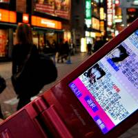 Desperate measures: A cell phone in Shibuya, Tokyo, shows an 'iede saito' (runaway site), where runaway girls post requests for a place to stay in return for sex. | YOSHIAKI MIURA PHOTO