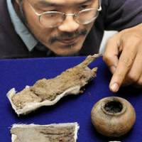 Rare find: Masahiro Ikeda, curator at the Hyogo Prefectural Museum of Archaeology, points Wednesday to a pot from an ancient makeup kit discovered in a tomb in Nishiwaki, Hyogo Prefecture. Above left is a rusty clod in which a pair of iron scissors and tweezers are embedded. Also in the picture is a Chinese bronze mirror.   KYODO PHOTO