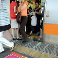 Safety in numbers: Women leave a female-only car on the JR Chuo Line at Yotsuya Station in Shinjuku Ward, Tokyo, in August. | SATOKO KAWSAKI PHOTO