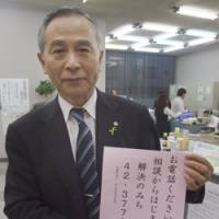 Toshiro Ozawa, welfare chief in Kurihara, Miyagi Prefecture, shows a leaflet reading: 'Please call us. Counseling is the first step on the way to solving your problem.' | AP PHOTO