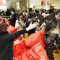 Grab and go: Customers snap up 'fukubukuro' lucky bags Monday at the Mitsukoshi department store in Nihonbashi, Tokyo. | KYODO PHOTO
