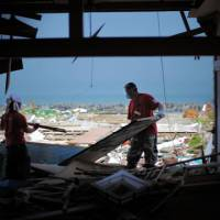 Growing spirit: Members of Team Heal Japan volunteer group clean up a home destroyed by the March 11 tsunami in Iwaki, Fukushima Prefecture, in June. | TEAM HEAL JAPAN