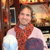 Knit-aid: Bernd Kestler shows off two of the knitted hats donated to his Knit for Japan initiative, which distributes such items to victims of the March 11 disasters, in Tokyo on Dec. 14. | KYODO