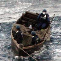Search and seizure: Japan Coast Guard personnel inspect a boat found Friday off Okinoshima Island in Shimane Prefecture. | KYODO