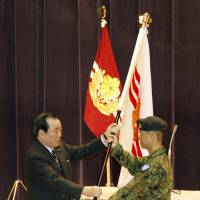 DinosDuty, honor, infrastructure: Defense Minister Yasuo Ichikawa at a ceremony Saturday in Tokyo hands a flag to a member of a Ground Self-Defense Force unit that will be sent to South Sudan. | KYODO