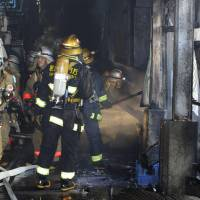 Fish fry: Fire engines sit outside Tsukiji fish market in Tokyo on Sunday as firefighters (left) attempt to extinguish a blaze that broke out after the market closed for the day. | KYODO