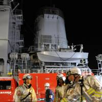 Shipboard blaze: Firefighters on Sunday respond to a fire on an MSDF fleet support ship in Kanagawa Prefecture. | KYODO