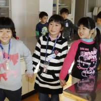 Orientation: A second-grade student (center) shows first-graders around Ota Elementary School in Minamisoma, Fukushima Prefecture, on Tuesday.   KYODO