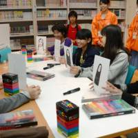 Career counseling: Professional manga artist Masahiro Muraoka (left) and local students show each other the characters they have drawn during the 'Mansai'manga festival in Kochi Prefecture in October. | KYODO PHOTOS
