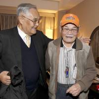 Together again: Minoru Ohye (right) and his younger brother, Hiroshi Kamimura, reunite in Kyoto on Monday after 60 years. | AP