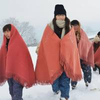 Snow-bound: Clad in traditional Japanese snow wear, Asian exchange students take part in a 'jifubuki' (drifting snow) tour Saturday in Goshogawara, Aomori Prefecture. | KYODO