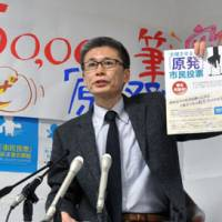 Sign of the times: Hajime Imai, secretary general of a group campaigning for plebiscites in Tokyo and Osaka on the continued operation of nuclear plants, faces reporters Jan. 9 to announce that more than 50,000 Osaka voters signed the petition. | KYODO