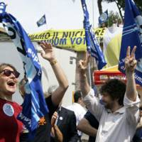 Italians celebrate after getting partial results of referendums where locals voted against reviving nuclear energy, in June. | AP