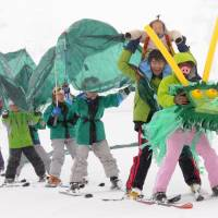 Fun on the slopes: A group of skiers led by Masahiro Kadoki (right) from Kurashiki, Okayama Prefecture, perform the dragon dance during a costume contest on Mount Daisen in Tottori Prefecture on Sunday. | KYODO