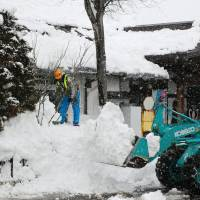 Snow where to go: A worker removes snow around JR Iiyama Station in Iiyama, Nagano Prefecture, on Tuesday. | KYODO