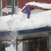 A man clears snow from the roof of a shopping arcade in Tokamachi, Niigata Prefecture, on Wednesday. A cold front has dumped heavy snow on extensive parts of Japan, killing at least 51 this winter. | KYODO PHOTO