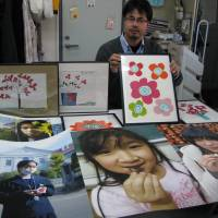 Drawn together: Maki Saito, secretary general of NGO JIM-NET, shows drawings by pediatric cancer patients in Iraq and photos of children from Fukushima Prefecture that are part of a Tokyo exhibit that started Wednesday. | KYODO