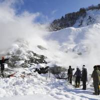 Grim aftermath: Authorities inspect the site Thursday where an avalanche leveled tents set up for bathers and killed three visitors to the Tamagawa Onsen inn in Senboku, Akita Prefecture. | KYODO