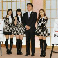 All in a day's work: Foreign Minister Koichiro Genba is all smiles as he poses Thursday with AKB48 girl group members (from left) Rie Kitahara, Yui Yokoyama and Tomomi Itano. | KYODO
