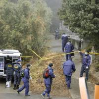 Grim hunt: Oita Prefectural Police officers search a wooded area Monday in Hiji where a bone fragment, possibly of a 2-year-old girl reported missing last fall, was found the previous day. | KYODO