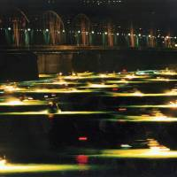 Eel deal: Fishing boats use bright lights to lure glass eel into their traps as they harvest the creatures by a bridge at the headwaters of the Yoshino River in the city of Tokushima. | KYODO