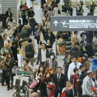 Terra firma: People crowd an arrivals lobby at Narita airport in Chiba Prefecture on Jan. 10.   KYODO